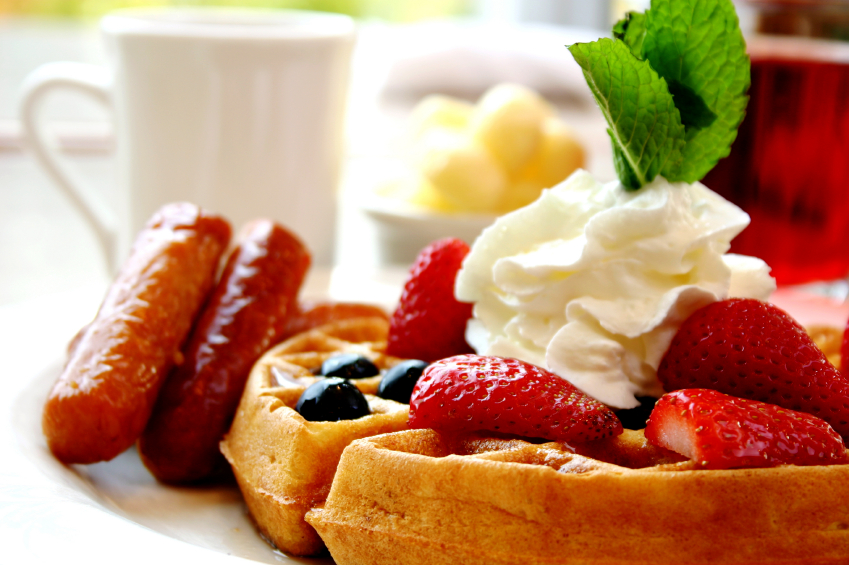 Blueberry waffles with strawberries and sausages