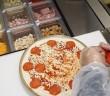Pizza preparada en mesa refrigerada